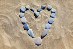 Heart made of stones in the sand. Royalty Free Stock Image