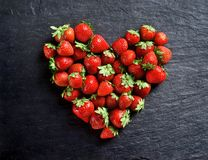Heart made of strawberry on black slate. Top view. High resolution product stock photography