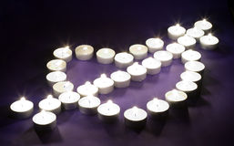 Heart made of tea lights on violet background Royalty Free Stock Image