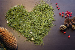 Heart made from tree needles. And other forest decor: pine and fir cones and dry berries. Top view on a wooden background Royalty Free Stock Photos