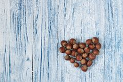 Hazel nuts heart Blue and whie Old grunge wooden background stock photography
