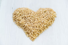 Heart made from wild brown rice on a wooden background Stock Images