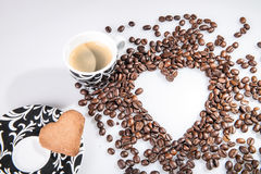 Heart make whit coffee beans and cup whit espresso and sweet heart cookie on white background. Stock Images