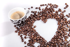 Heart make whit coffee beans and cup whit espresso and sweet heart cookie on white table background. Royalty Free Stock Photos