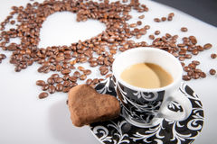 Heart make whit coffee beans and cup whit espresso and sweet heart cookie on white table background. Royalty Free Stock Images