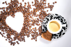 Heart make whit coffee beans and cup whit espresso and sweet heart cookie on white table background. Stock Photo