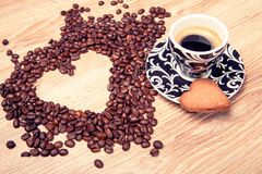 Heart make whit coffee beans and cup whit espresso and sweet heart cookie on wood table background. Stock Images