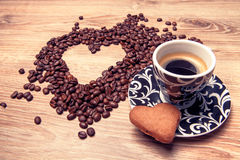 Heart make whit coffee beans and cup whit espresso and sweet heart cookie on wood table background. Royalty Free Stock Photos