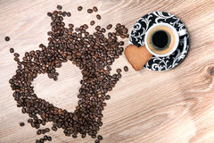 Heart make whit coffee beans and cup whit espresso and sweet heart cookie on wood table background. Royalty Free Stock Photography