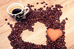 Heart make whit coffee beans and cup whit espresso and sweet heart cookie on wood table background. Royalty Free Stock Photo