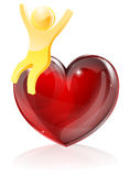 Heart man concept. Of a happy person with arms raised sitting on a giant heart Royalty Free Stock Photo