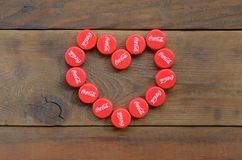 Heart of many red caps with coca cola logo on wooden background