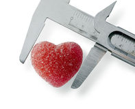 Measuring heart. Heart measured with caliper. Isolted over white background Royalty Free Stock Photography