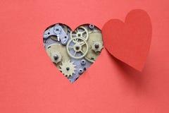 Heart Mechanism. Old clock mechanism inside open heart cutting from red paper stock photo