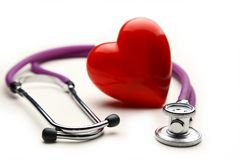 Heart with a medical stethoscope, isolated on wooden background royalty free stock images