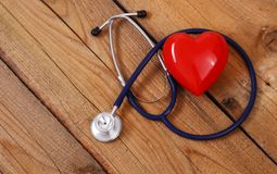 Heart with a medical stethoscope, isolated on wooden background. A heart with a medical stethoscope, isolated on wooden background stock photos