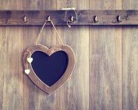 Heart Menu Board. Heart shape menu board hanging on wooden panel wall - vintage tone effect added to wood Royalty Free Stock Photo