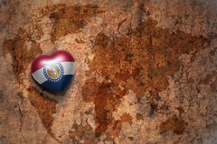 Heart with missouri state flag  on a vintage world map crack paper background. Concept Stock Photography