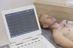 Heart monitoring with electrocardiogram equipment making cardiogram test to male patient in hospital clinic royalty free stock images