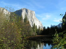 El Capitan behind lake and trees. Morning sun warms the face of El Capitan Royalty Free Stock Photography