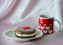 Heart mug with pastry. Pink and white chocolate is drizzled over a chocolate cake whoopee pie, filled with white cream and topped with a jelly red heart. paired Stock Images
