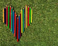 Heart of multicolored pencils on the grass. Heart of multicolored pencils on the laying on the grass background royalty free stock photo