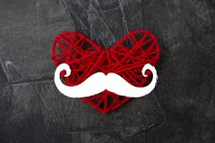 Heart with a mustache on a dark background.