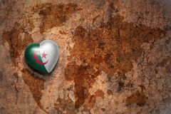 Heart with national flag of algeria on a vintage world map crack paper background. Concept Stock Photos