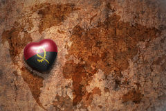 Heart with national flag of angola on a vintage world map crack paper background. Concept Royalty Free Stock Image