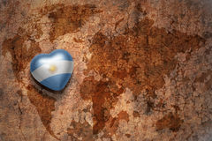 Heart with national flag of argentina on a vintage world map crack paper background. royalty free stock image