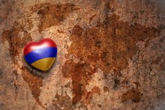 Heart with national flag of armenia on a vintage world map crack paper background. Concept Royalty Free Stock Photos