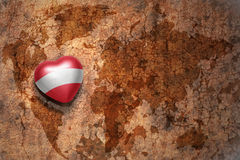 Heart with national flag of austria on a vintage world map crack paper background. Concept Royalty Free Stock Photo