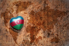 Heart with national flag of azerbaijan on a vintage world map crack paper background. Stock Photography