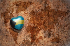 Heart with national flag of bahamas on a vintage world map crack paper background. Concept Royalty Free Stock Image
