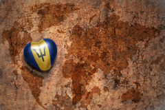 Heart with national flag of barbados on a vintage world map crack paper background. Concept Royalty Free Stock Photo