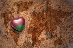 Heart with national flag of belarus on a vintage world map crack paper background. Concept Royalty Free Stock Image
