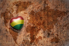Heart with national flag of bolivia on a vintage world map crack paper background. Concept Stock Photography