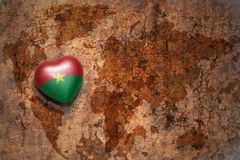 Heart with national flag of burkina faso on a vintage world map crack paper background. Concept Royalty Free Stock Image