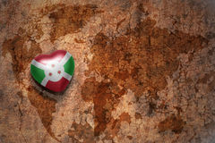 Heart with national flag of burundi on a vintage world map crack paper background. Concept Stock Photo