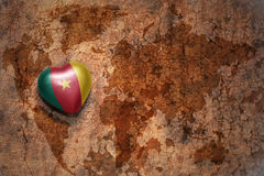 Heart with national flag of cameroon on a vintage world map crack paper background. Concept Stock Image