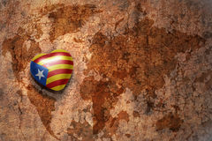 Heart with national flag of catalonia on a vintage world map crack paper background. Concept Stock Images
