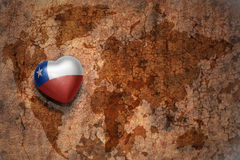 Heart with national flag of chile on a vintage world map crack paper background. Concept Royalty Free Stock Photos