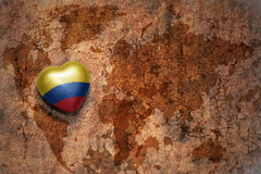 Heart with national flag of colombia on a vintage world map crack paper background. Concept Royalty Free Stock Photos