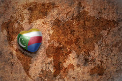Heart with national flag of comoros on a vintage world map crack paper background. Concept Stock Image