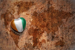 Heart with national flag of cote divoire on a vintage world map crack paper background. Concept Royalty Free Stock Image