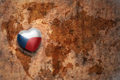 Heart with national flag of czech republic on a vintage world map crack paper background. Concept Royalty Free Stock Images