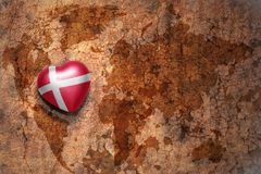Heart with national flag of denmark on a vintage world map crack paper background. Concept Stock Photos