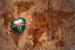 Heart with national flag of dominica on a vintage world map crack paper background. Concept Stock Photos