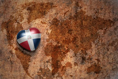 Heart with national flag of dominican republic on a vintage world map crack paper background. Royalty Free Stock Photos