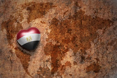 Heart with national flag of egypt on a vintage world map crack paper background. Concept royalty free stock photo